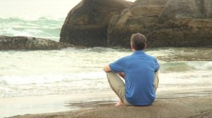 stock-footage-hd-i-man-relaxing-while-sitting-on-a-rock-at-the-sea